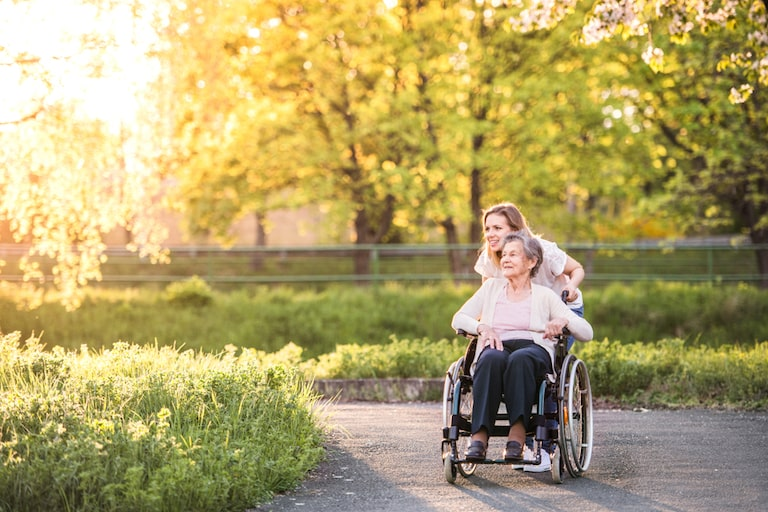 badante convivente vitto e alloggio accompagna un'anziana su sedia a rotelle in un parco