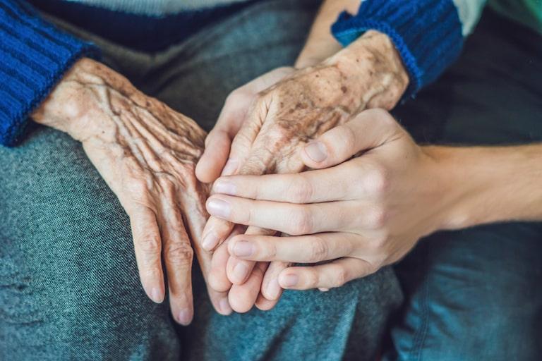 bonus colf e badanti 2021: mani di una donna anziana e di una giovane che si intrecciano