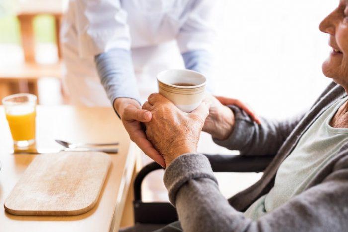 costi badante non convivente: una badante aiuta l'assistito a bere