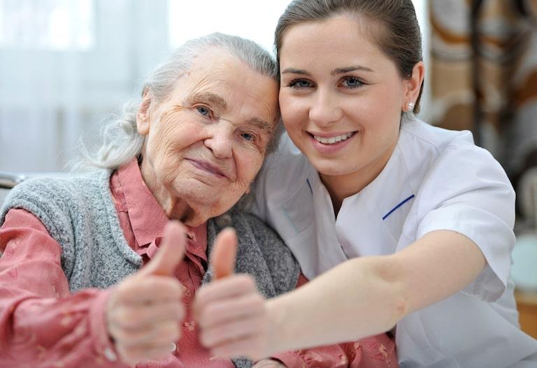 quanto costa una badante: anziana e badante che fanno il gesto del pollice verso l'alto