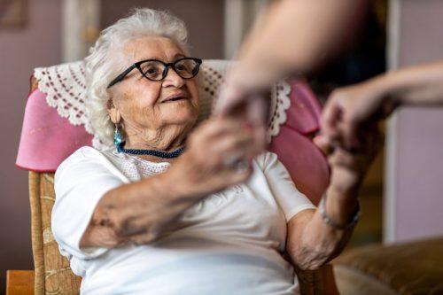 quanto si paga una badante: badante aiuta un'anziana ad alzarsi dalla poltrona